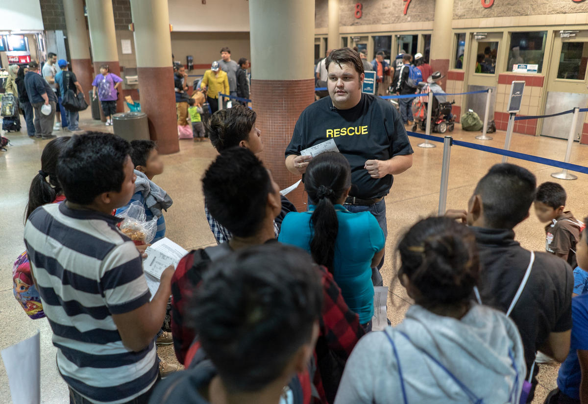 IRC staff member helping Central Americans find their buses