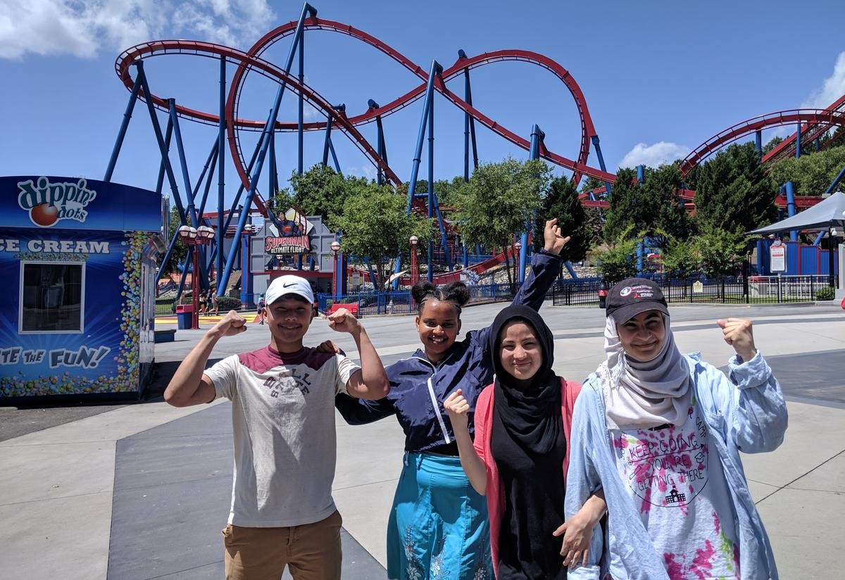 Four students post for a picture in front of a large rollercoaster.