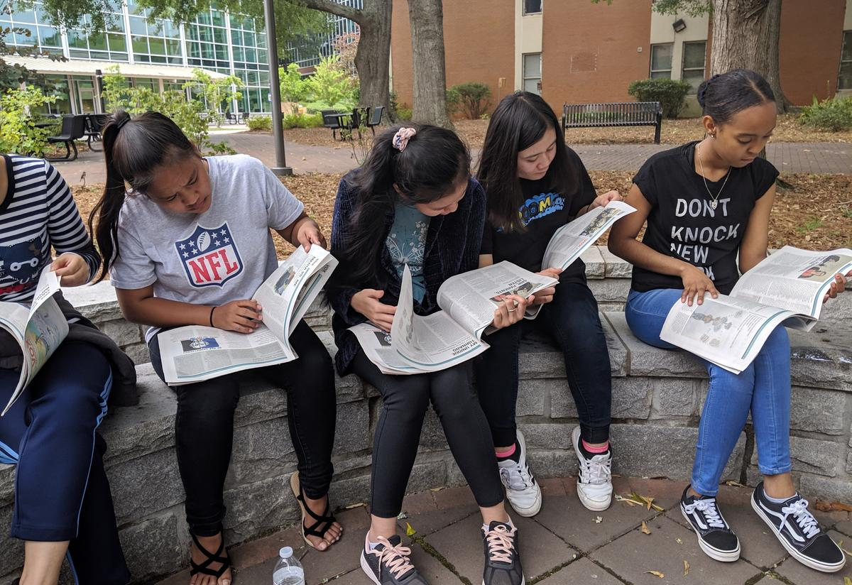 Four students are reading teen newspapers outside on a college campus.