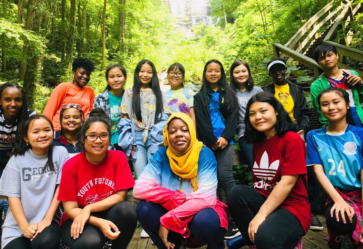 Students and staff take a group picture outside, surrounded by trees.