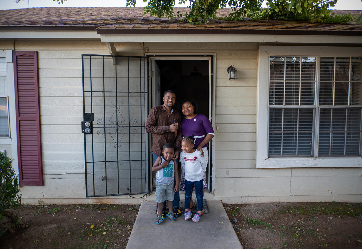 Robert, 28, and his wife Esther, 25, stand with their two children in the doorway of their home in Phoenix