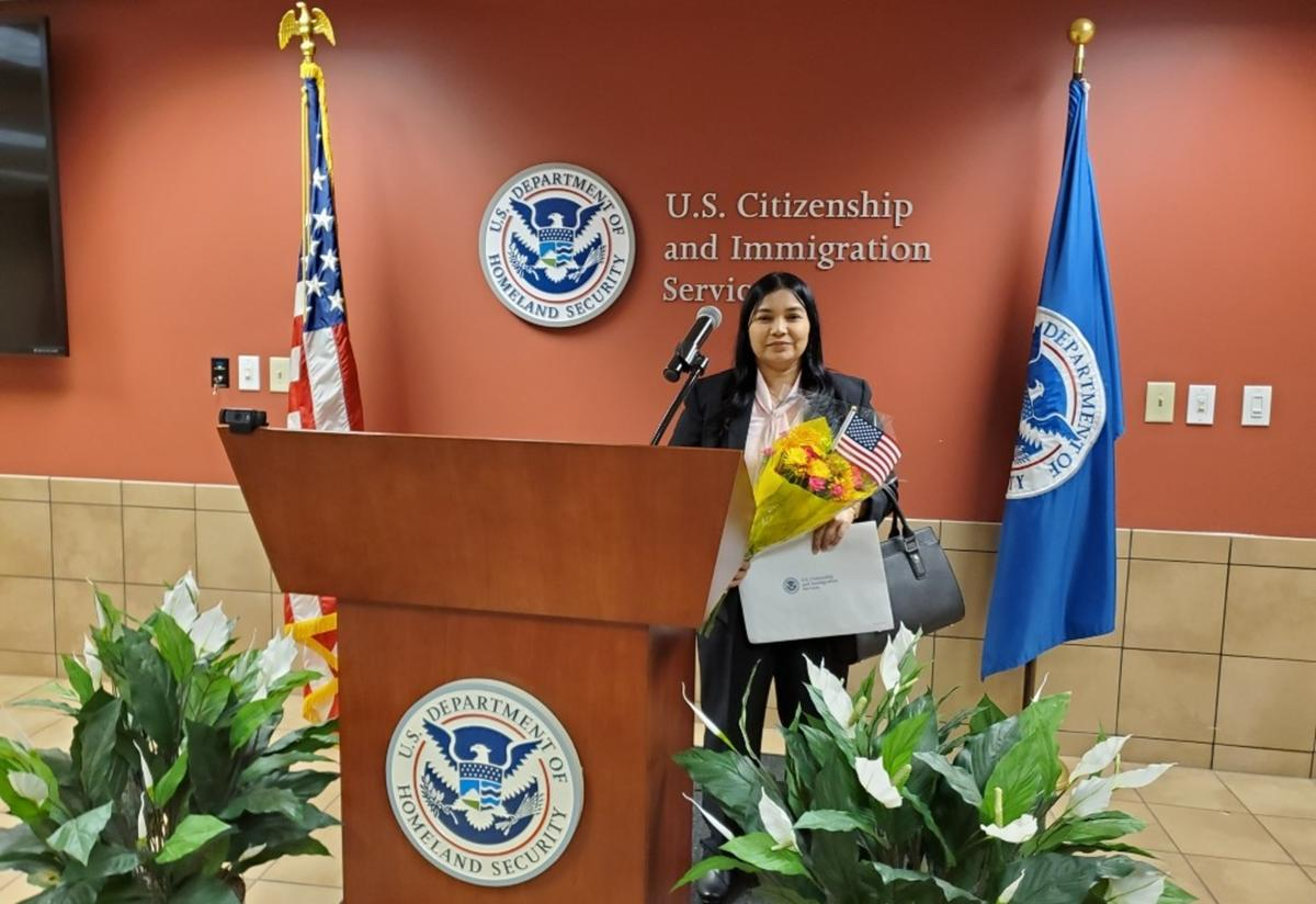 """A short woman with dark hair stands behind a podium holding a bouquet of flowers and a paper certificate. The words """"United States Citizenship and Immigration Services"""" are on the wall behind her."""