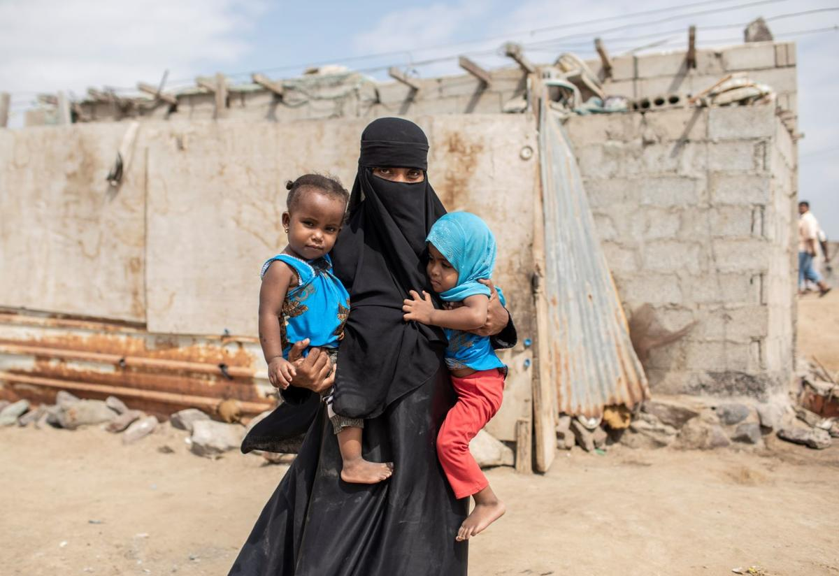 A displaced woman stands holding her toddler twin daughters outside the house they rent at a settlement for displaced people on the outskirts of Aden, Yemen.