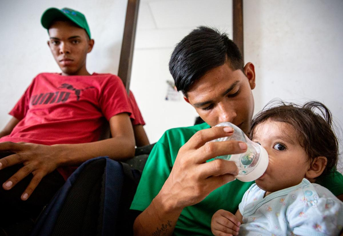 A baby is bottle-fed by her 15-year-old cousin, a Venezuelan refugee in Colombia. The family was supported by the IRC.