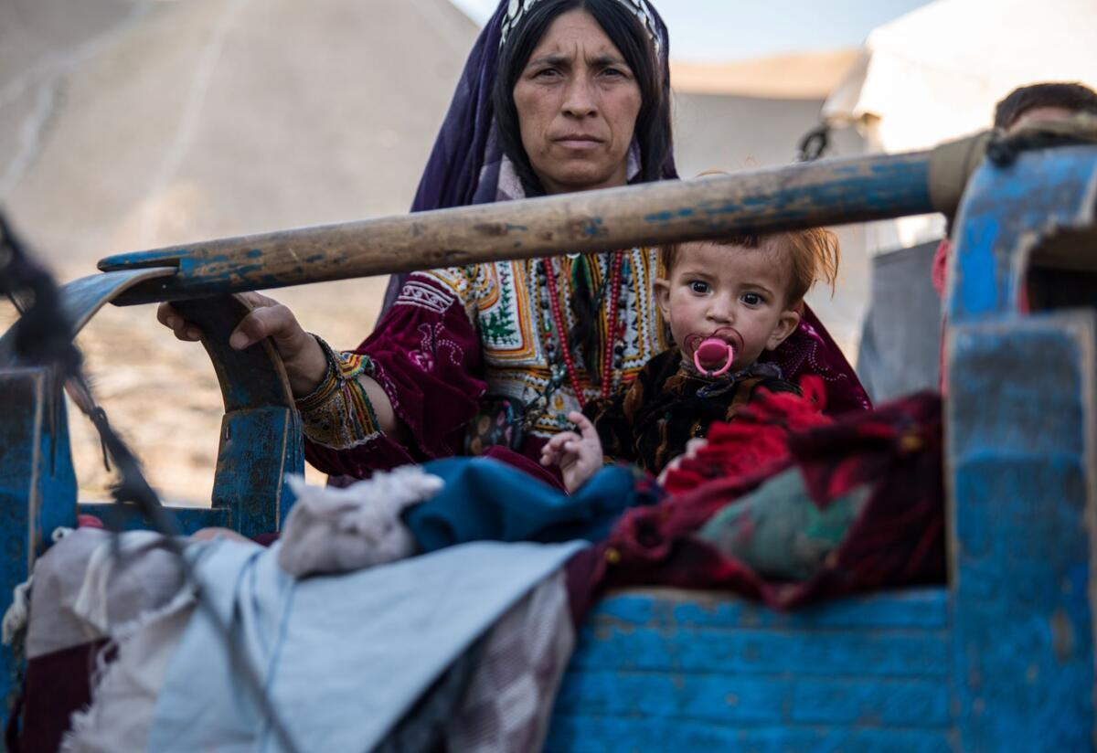 A mother rocks her sick child, who is sucking on a pacifier, in a camp in Afghanistan's Badghis province, where the IRC supports displaced families.