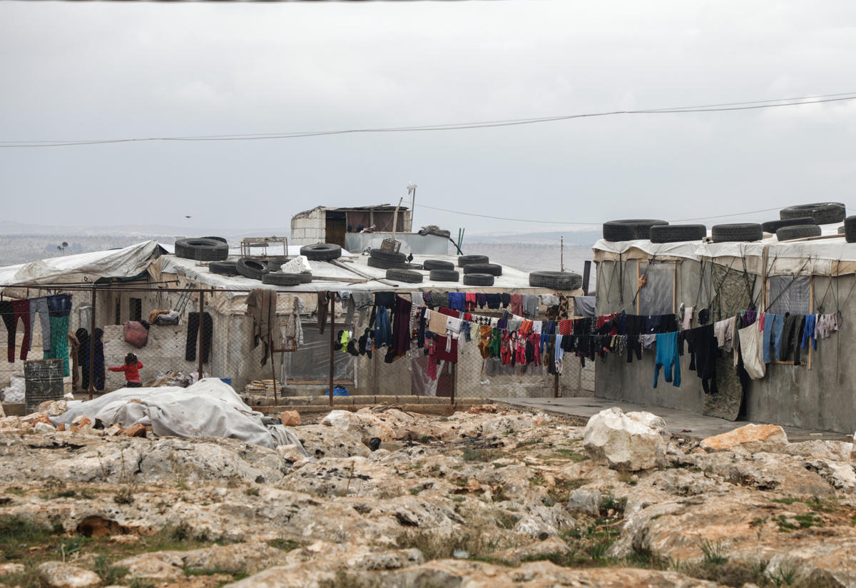 Clothes hang in settlement for displaced Syrians on outskirts of Deir Hassan in Idlib