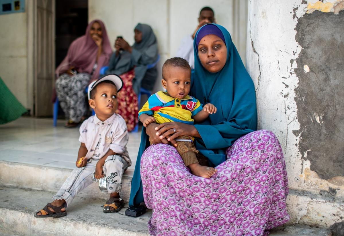 A displaced woman assisted by the IRC sits with her children in Somalia.