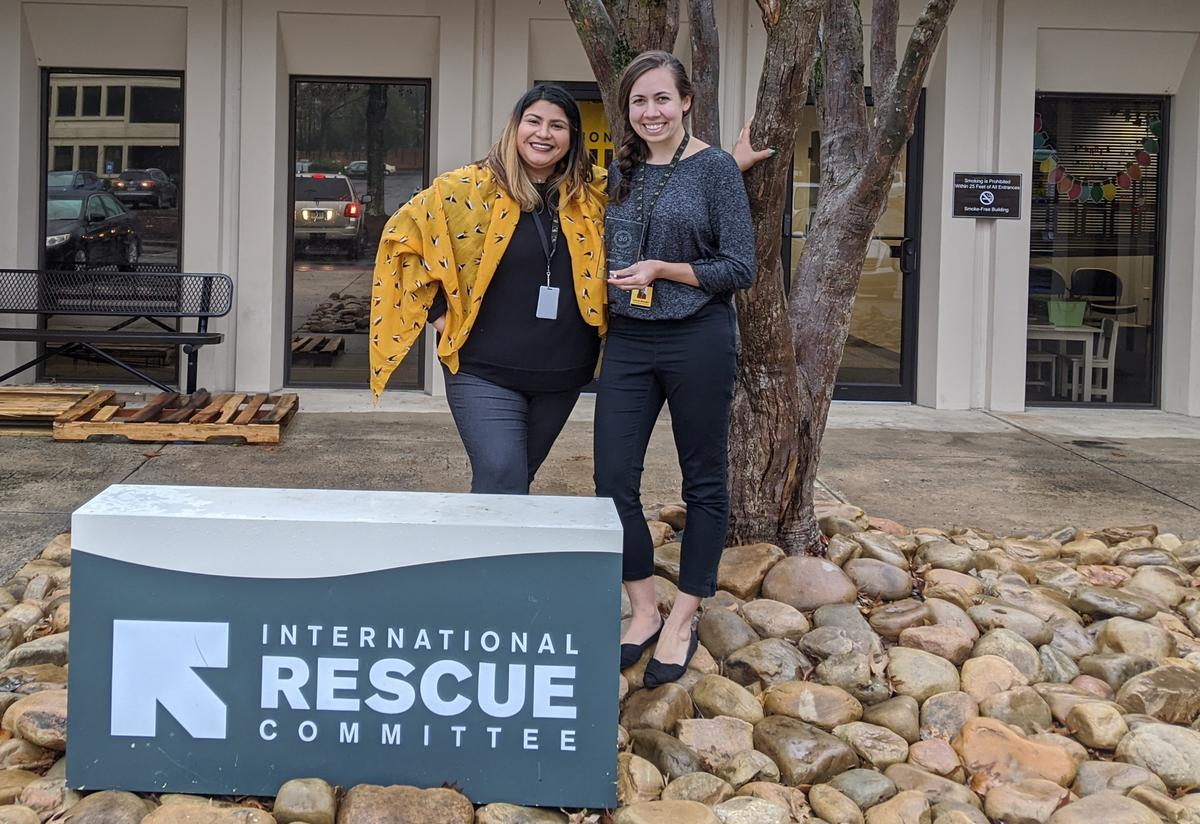 Two women stand beside a large sign that says International Rescue Committee and just in front of a medium sized tree. They are smiling and holding glass awards. They wear lanyards and work badges around their necks.