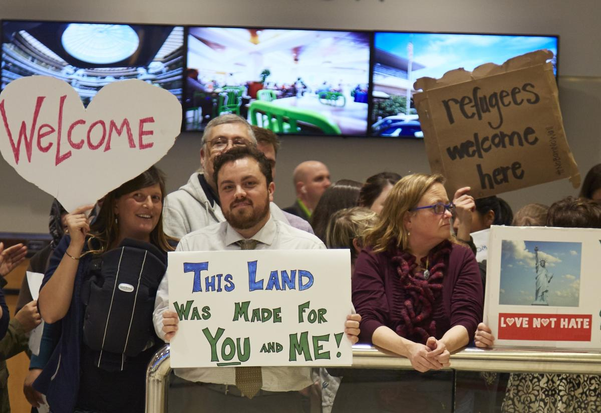 People holding different signs that say Welcome, This Land Was Made for You and Me, and Refugees Welcome stand behind an airport guard rail.