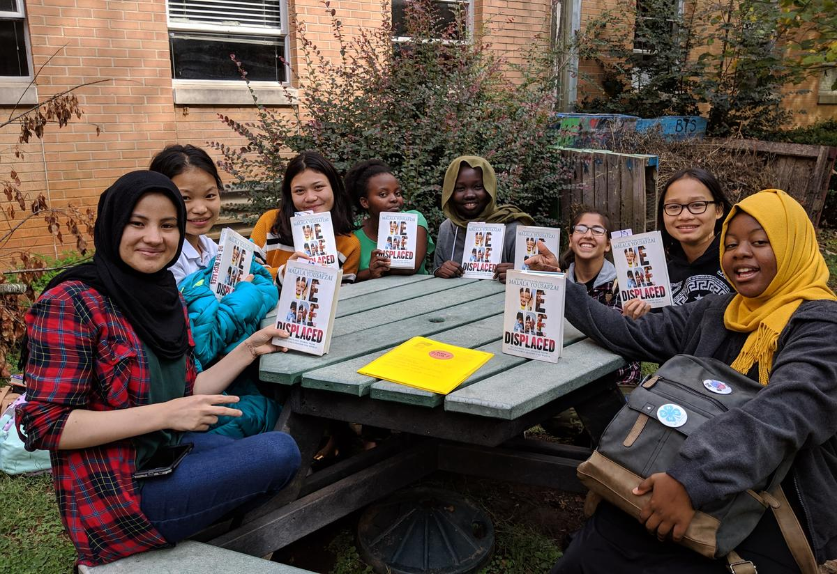 A diverse group of high school age girls are sitting around an outdoor picnic table and holding copies of Malala Yousafzai's most recent book.