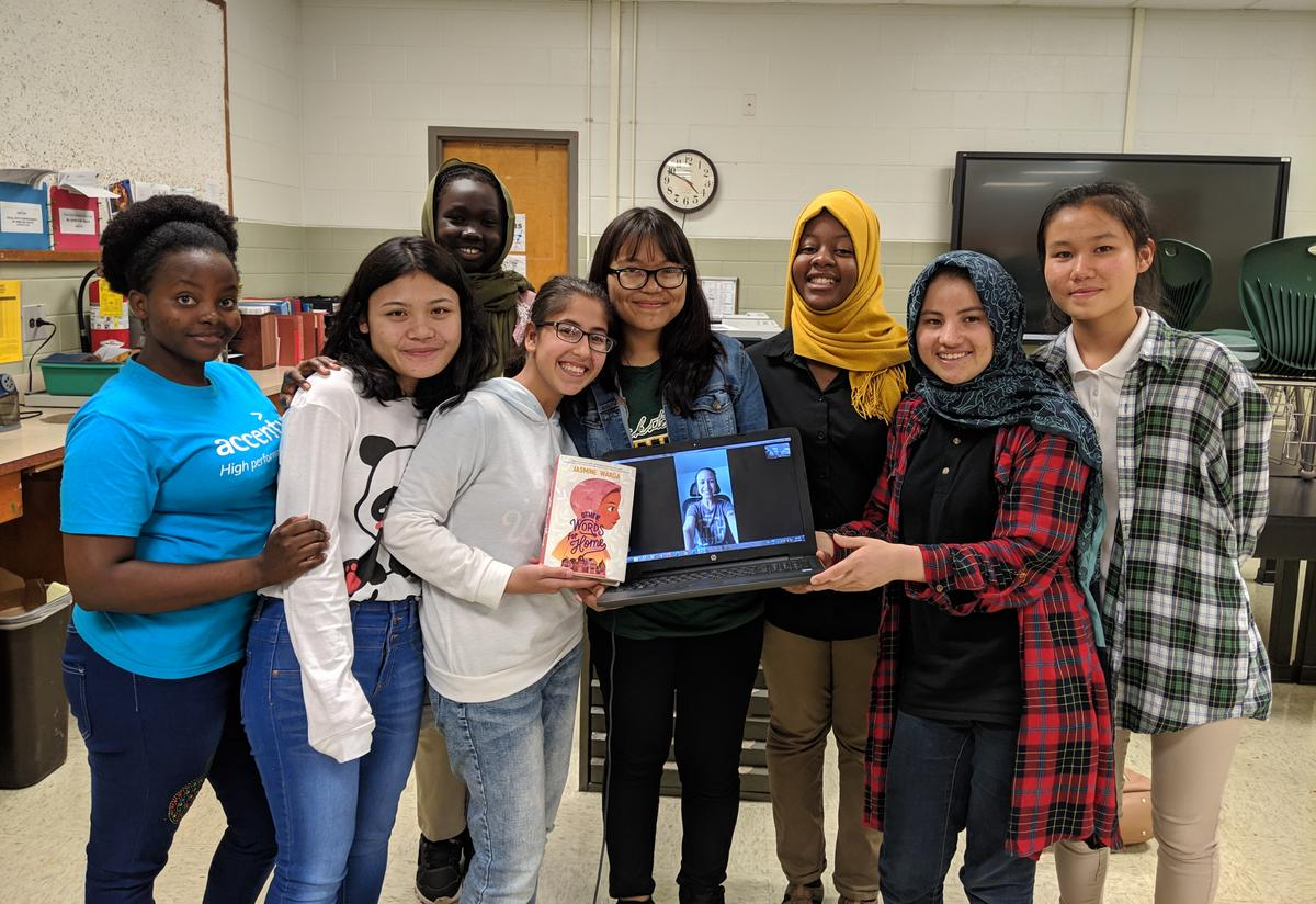 A diverse group of female high school students are standing together in a classroom. One student holds a laptop with an open Skype call and author Jasmine Warga is on the screen.