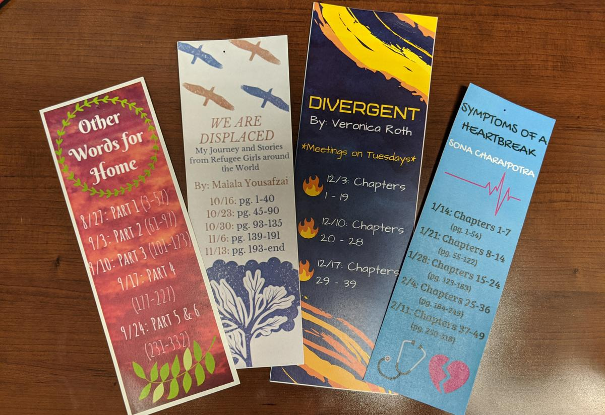 Four colorful bookmarks are arranged on a desk. Each bookmark has the name and author of a different book, as well as a reading schedule for the students to follow.