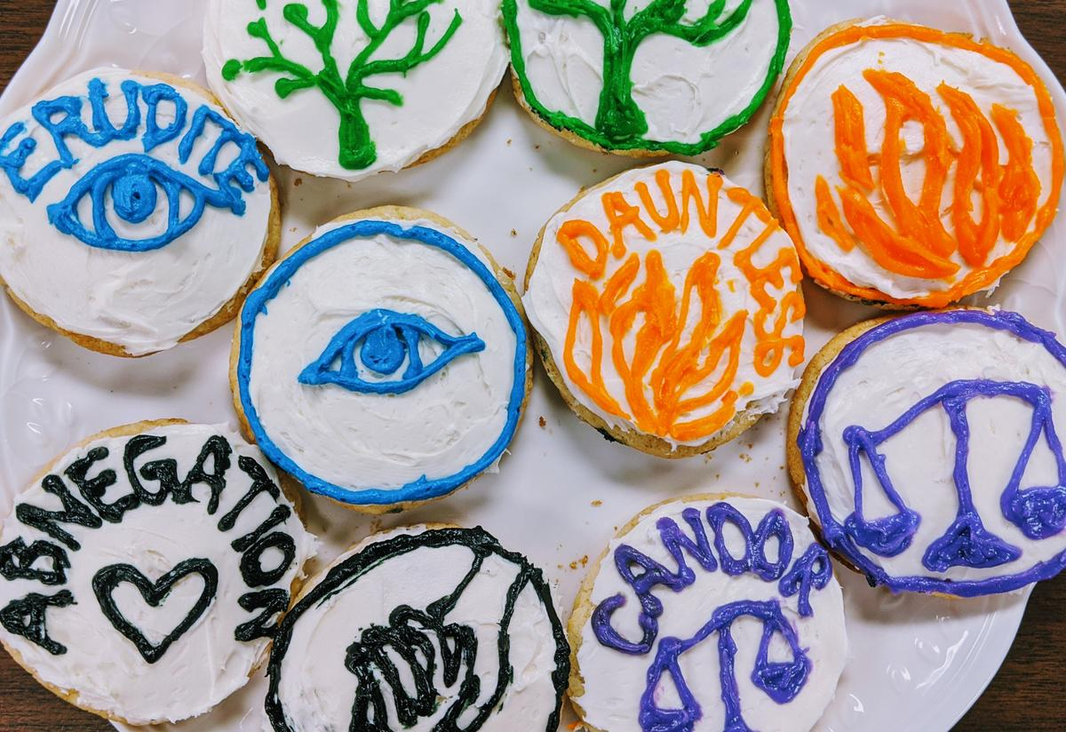 A plate of colorful, iced cookies with symbols including a tree, an eye, fire and scales, representing the factions from the book.