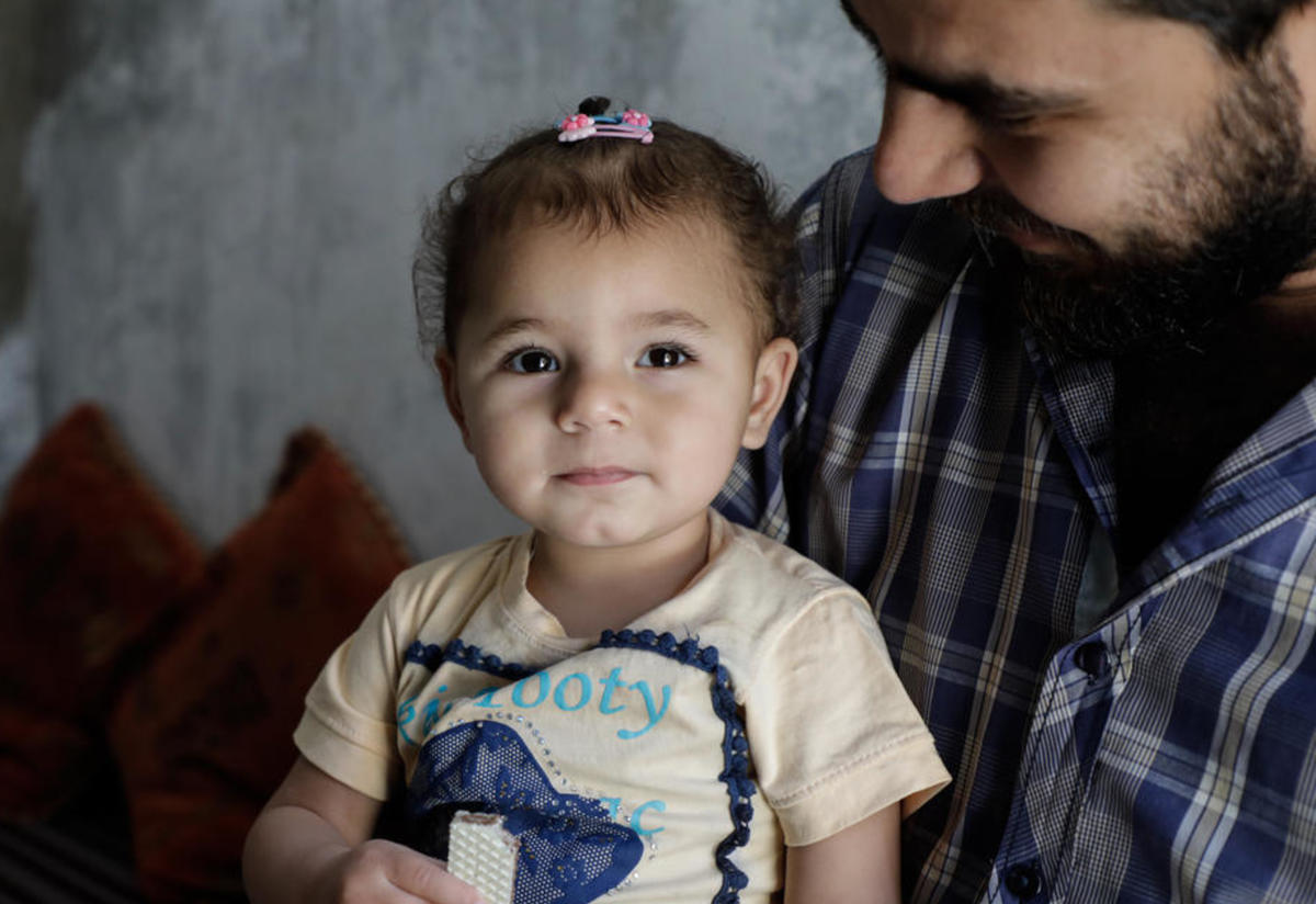 A 32-year-old man holds his 1 1/2 year-old daughter in Armanaz town in western Idlib.
