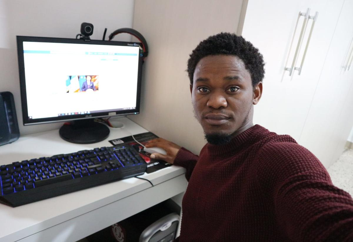 Henry, a Refugee.Info moderator, poses in front of his computer while sharing vital information with refugees and asylum seekers in Italy.