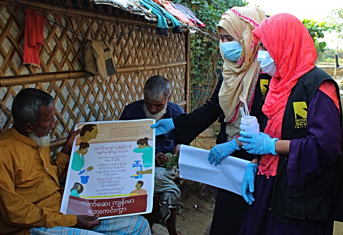 Community Health Volunteers in Bangladesh hold a poster and talk to a community member about COVID-19.