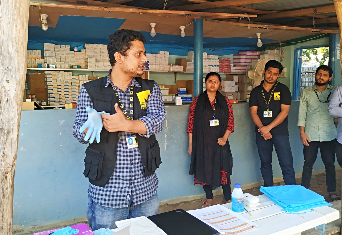 An IRC doctor demonstrates the proper way to put on gloves for health care workers and volunteers in an IRC health facility in Bangladesh.