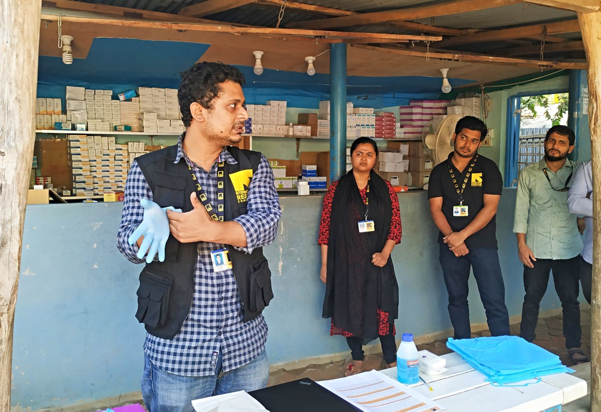 Dr. Mahmud puts on a glove to demonstrate the proper technique, while health workers and health volunteers watch him.