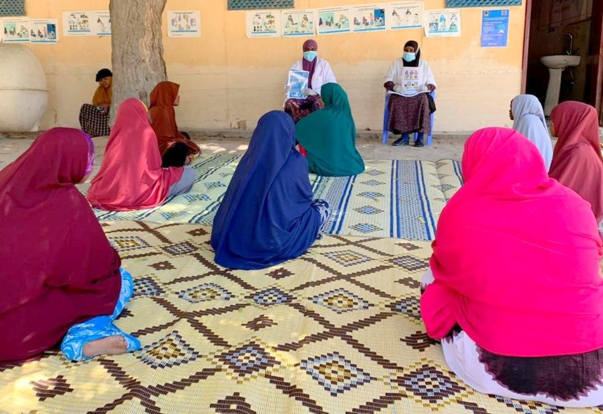 Two health workers in masks speak to a group of women about the coronavirus in a health clinic in Mogadishu, Somalia.