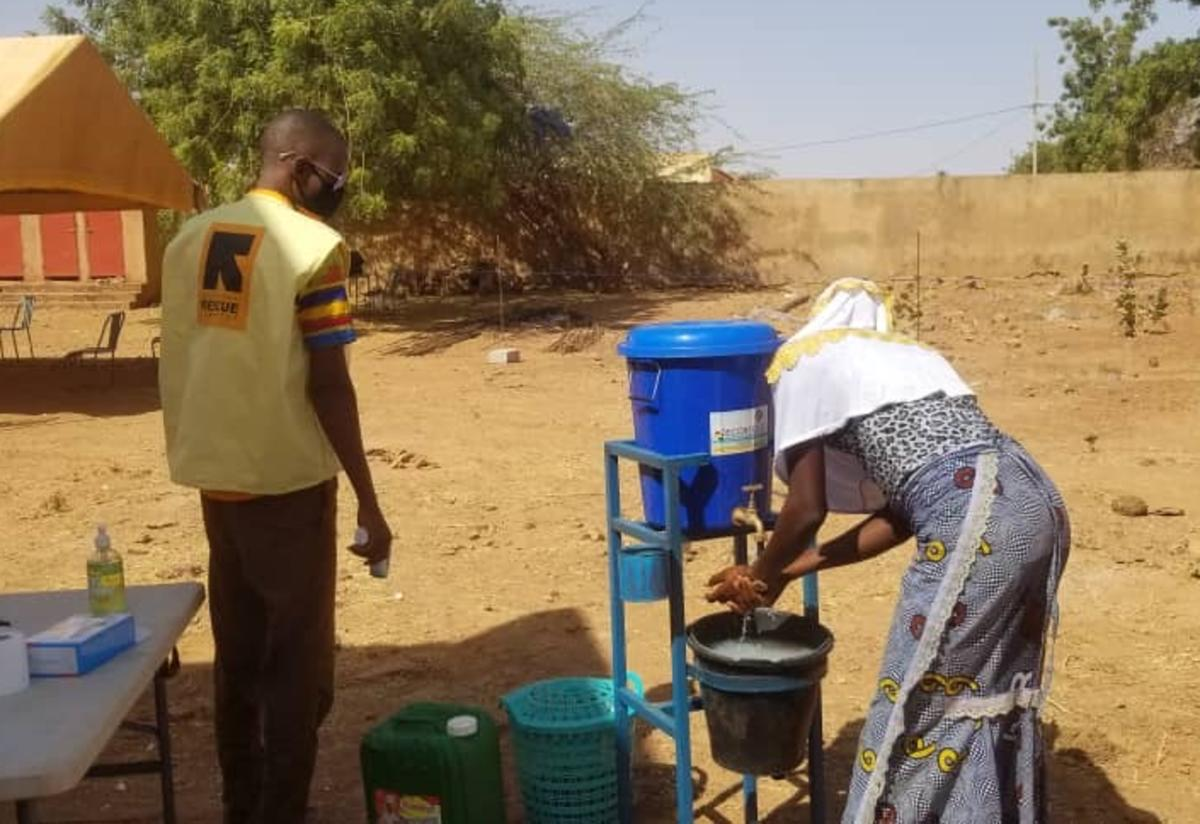 A woman washes her hands while an IRC staff member looks on in Burkina Faso