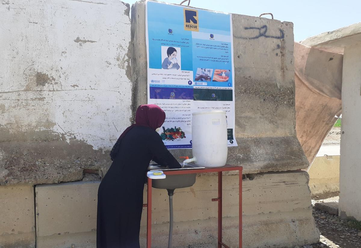 A woman washes her hands at an IRC handwashing station with an informational poster on a wall above her head.