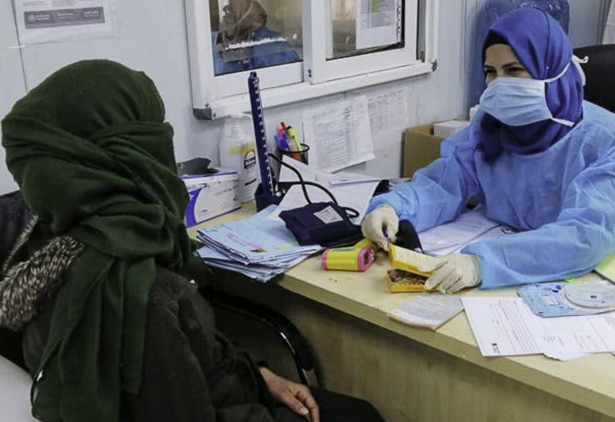 An IRC midwife wearing Personal Protective Equipment, or PPE, sits at a desk and talks with an IRC client.