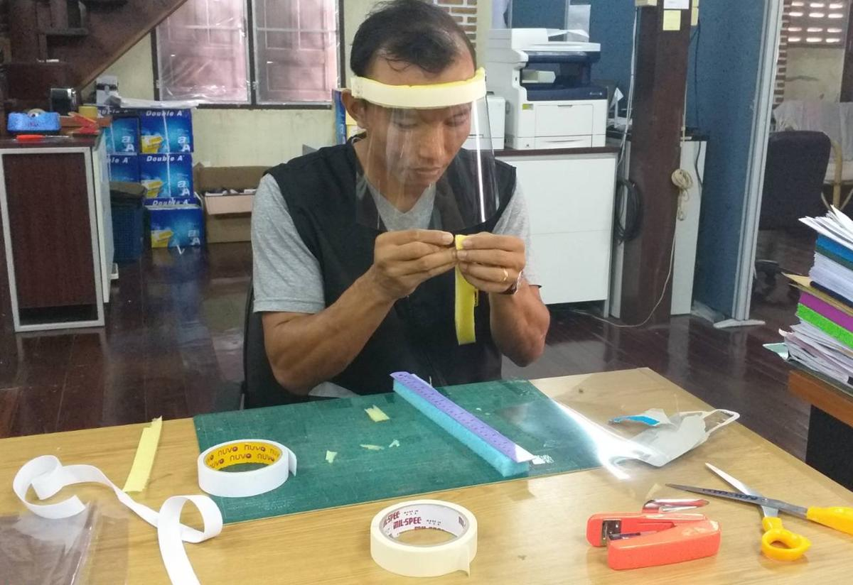 An IRC staff member in a refugee camp in Thailand sits at a desk wearing a face shield. The desk has scissors, a ruler, and tape, and he is using the supplies to create face shields.
