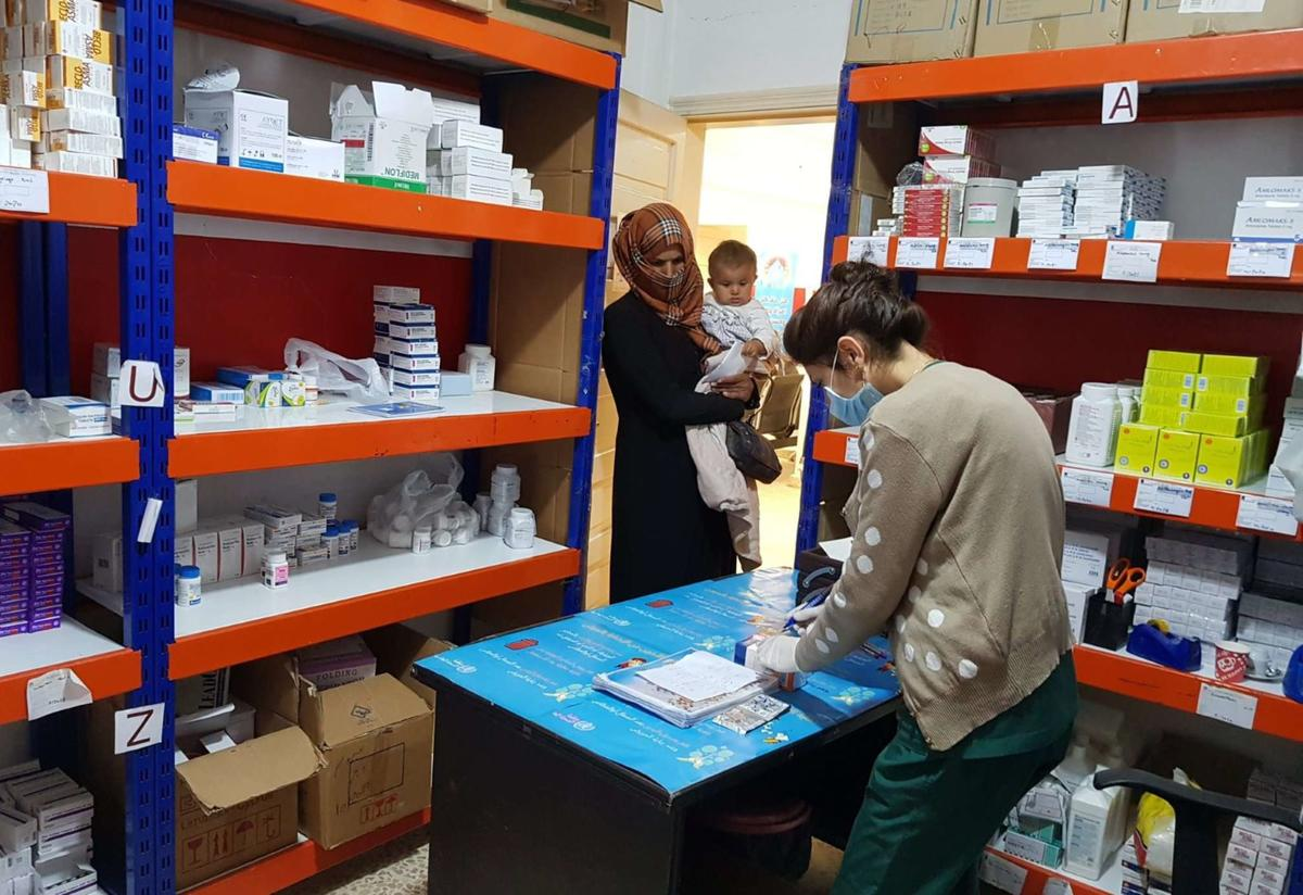 At a pharmacist in NE Syria, a pharmacist wearing a mask and gloves prepares medication while a mother holding a baby waits to get her medicine.