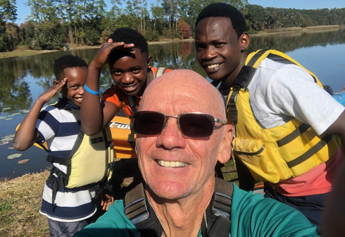 Tommy takes a selfie of him with his mentees and their brother by the river. The three young boys pose behind him and are smiling and wearing life jackets.