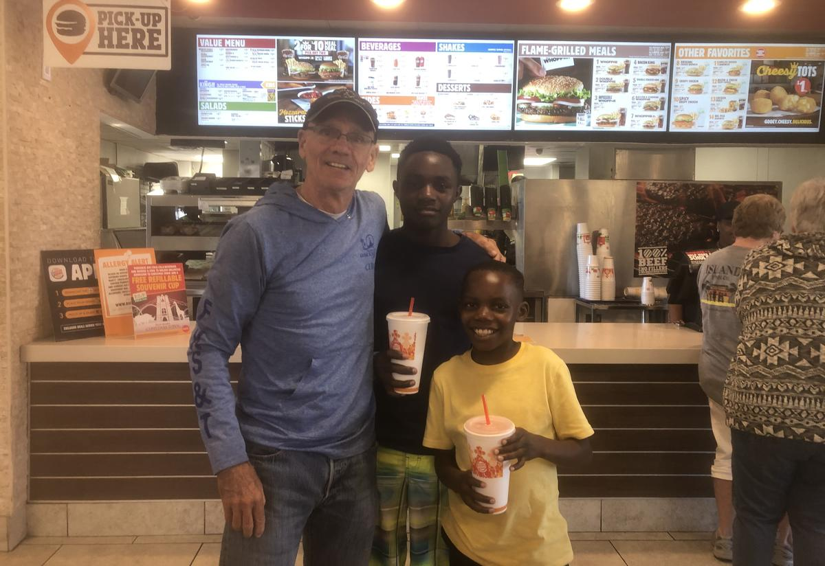 Tommy stand with his arm around Eric and Emmanuel in front of the Burger King counter. The boys hold large sodas and are smiling.