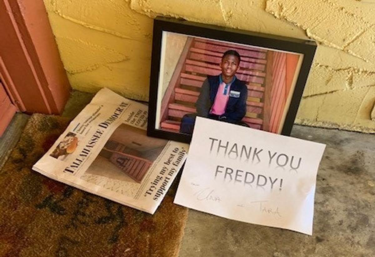 """A newspaper with a picture of a young man on the front page, a framed copy of that photo and a sign that says """"Thank You Freddy"""" are left on a doormat outside Freddys home."""