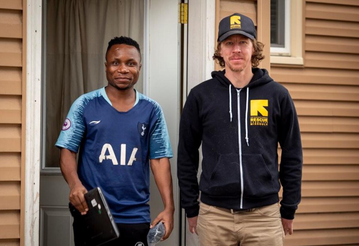 An IRC staff member stands next to an IRC client holding a laptop.