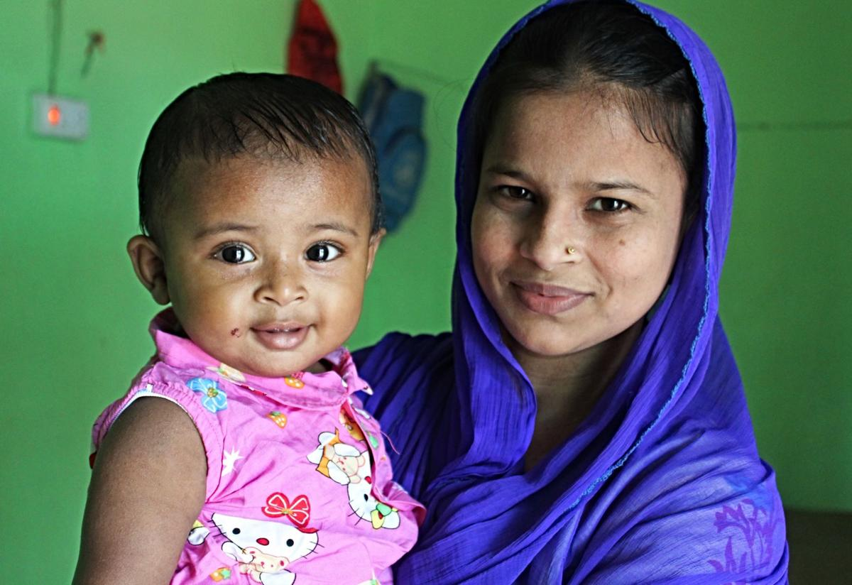 Lovely Akter, an IRC midwife, poses with her nine-month-old daughter. Lovely is wearing a blue headscarf and her daughter is wearing a pink shirt. Both are smiling.