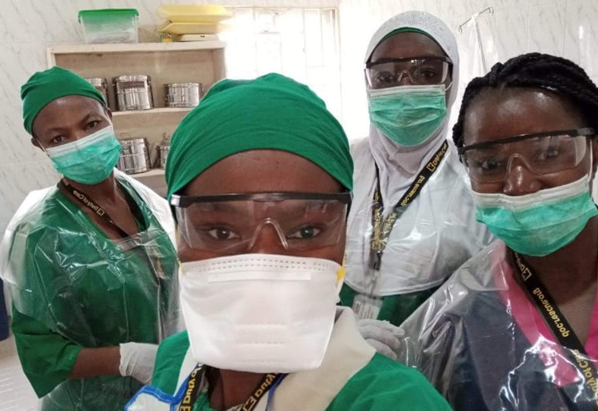 Four midwives wearing scrubs and personal protective equipment (PPE), including masks, take a selfie at the reproductive health clinic in Bakassi Internally Displaced Person (IDP) camp in Maiduguri, Nigeria.