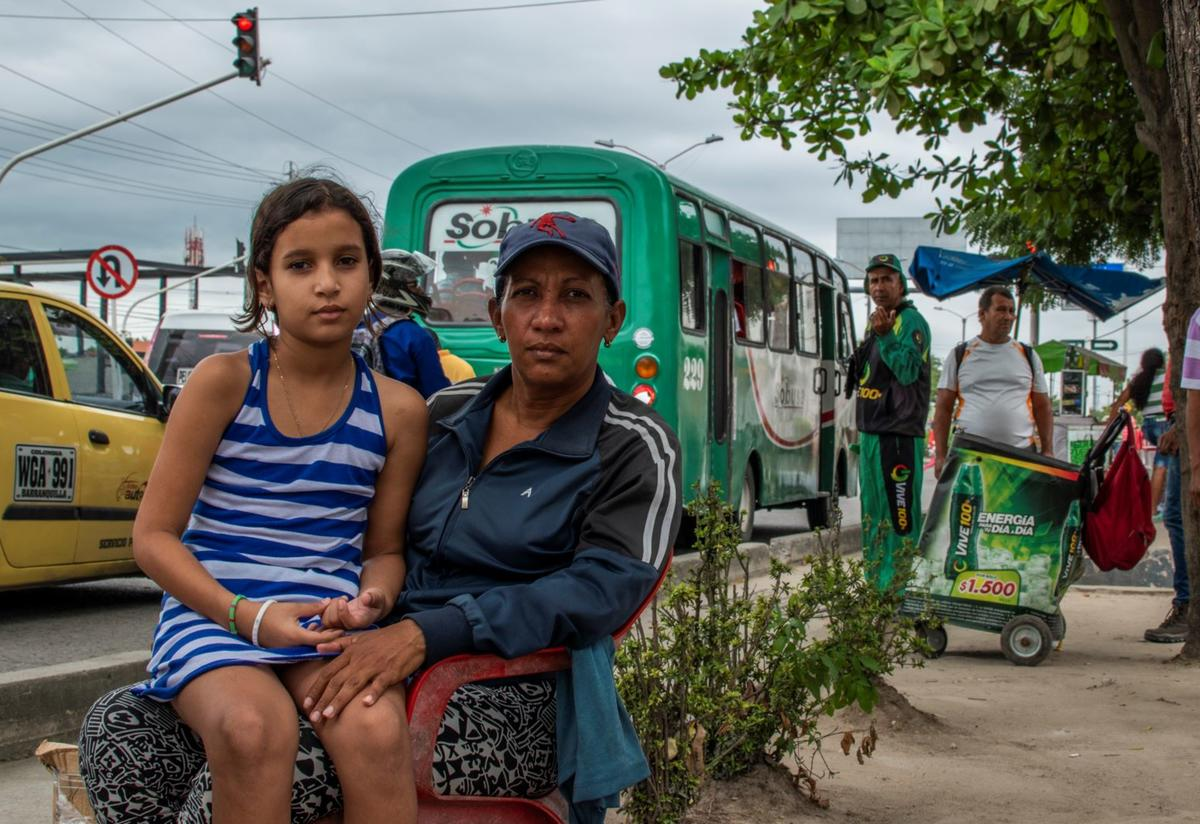 Venezuelan mother Karina sits with her ten-year-old daughter Geicelis on her lap. They are sitting outside looking at the camera. There is a green bus behind them.