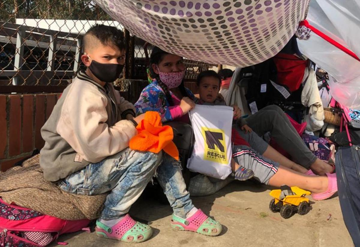 A mother with two kids sit under a makeshift tent surrounded by their luggage. They are all wearing masks and are looking directly at the camera.
