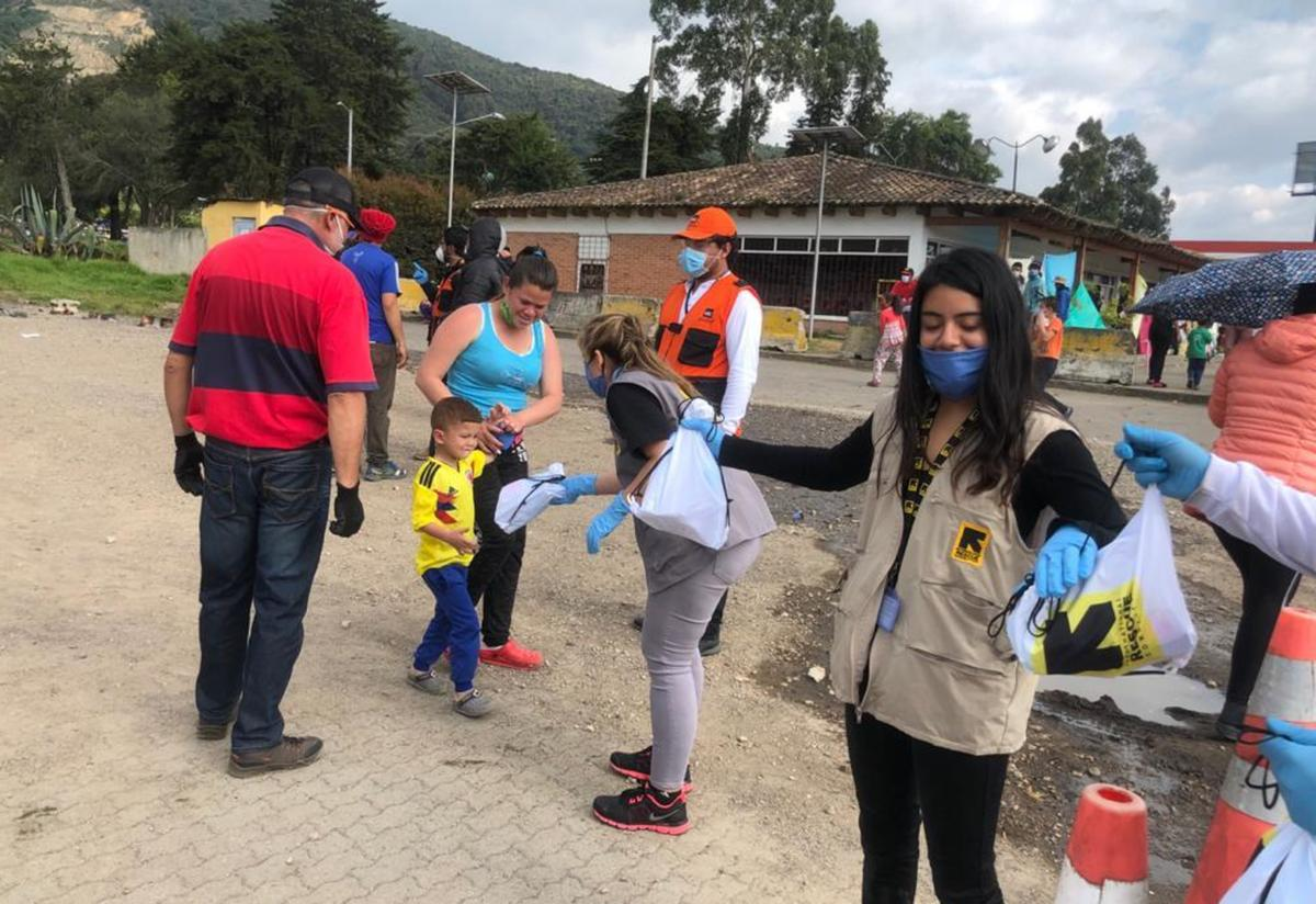 Two IRC staff members stand in a line passing out supplies outside near the Bogota-Chia highway. A family, including a young boy, are given supplies.