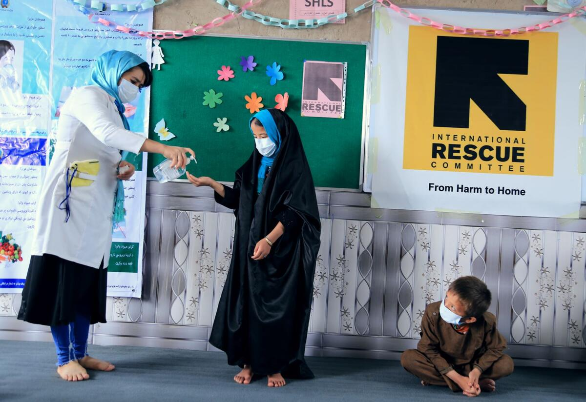 IRC hygiene promoter Sohalia Khaliqi, wearing a mask, squirts hand soap onto the hand of a child, also wearing a mask, while another child looks on. She is providing training and critical information about COVID-19 in Herat province, Afghanist