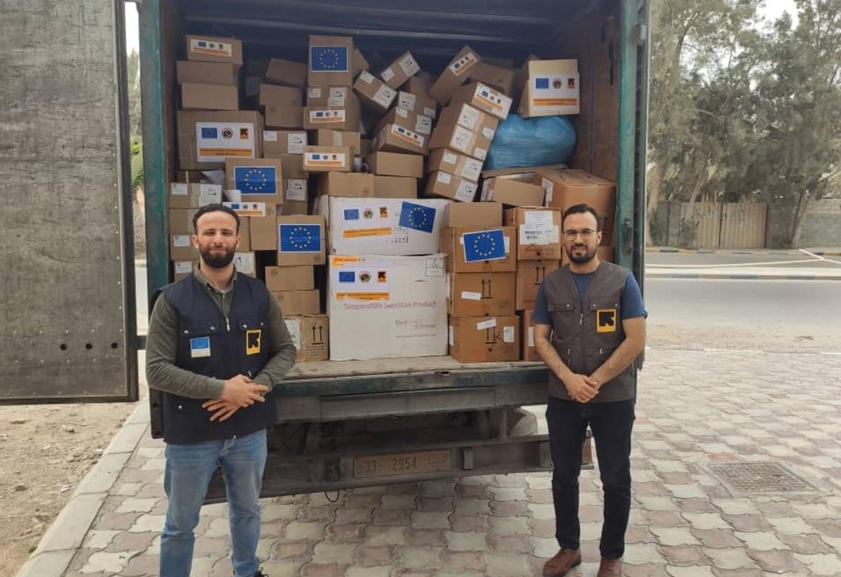 Two men wearing IRC vests stand in front of a truck full of boxes of supplies to fight COVID-19, in Libya.