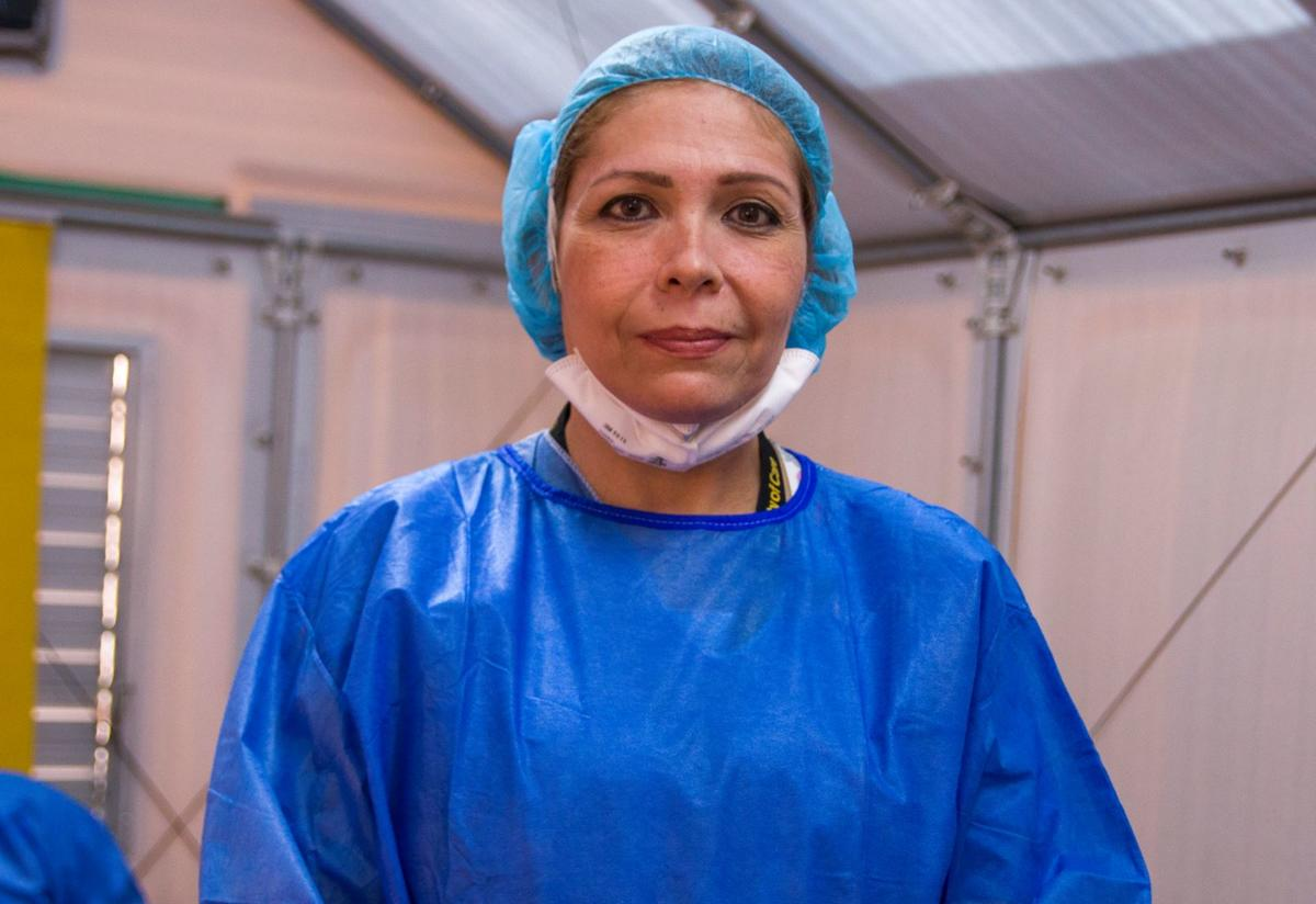 Dr. Eda Patricia Gomez, wearing bright blue scrubs and looking straight at the camera.