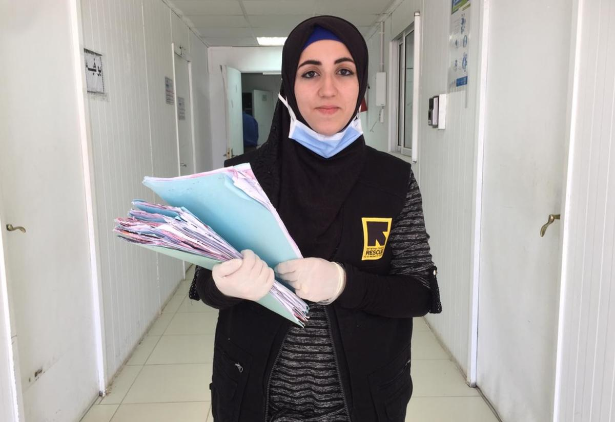 Doha Ibrahim Ammouri, holding files, walks in a hallway in an IRC reproductive health clinic. She is wearing a mask and gloves.