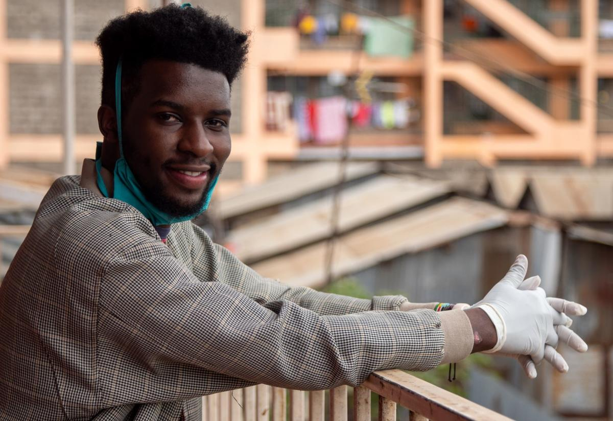 Jean Marie Ishimwe, a youth advocate and Rwandan refugee living in Kenya, leans against a railing with buildings behind him.