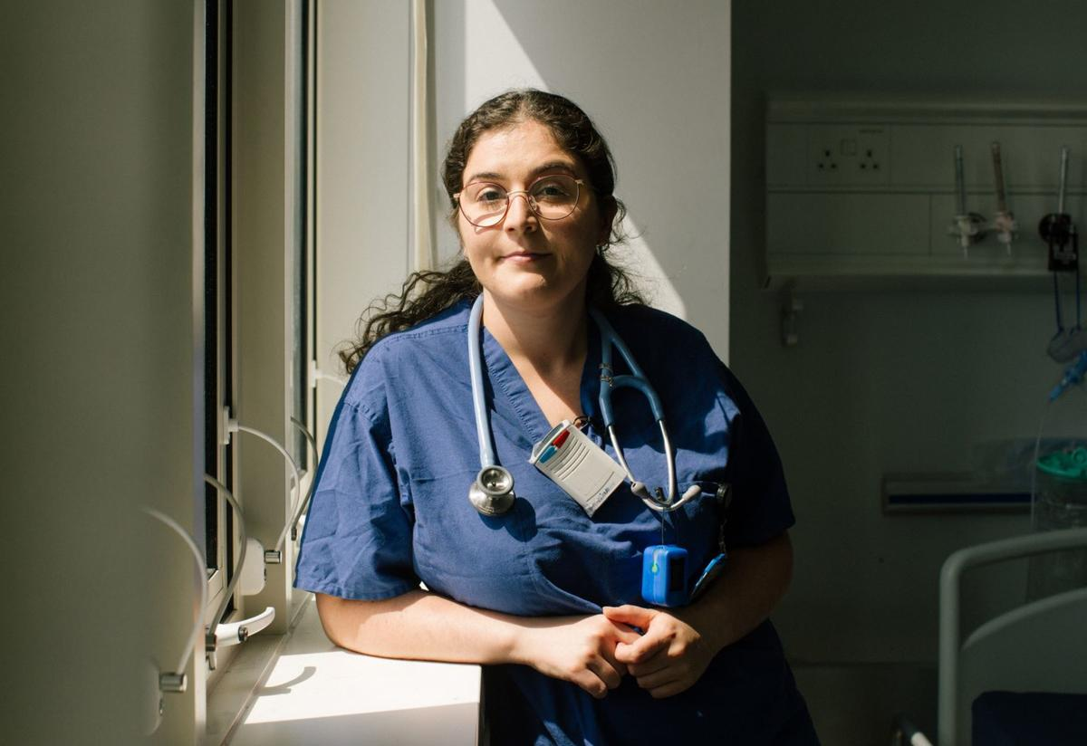Anxhela poses in her scrubs by a window. She is wearing a stethoscope.