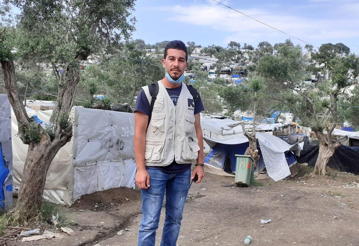Shadi stands in front of a tree and a tent in a refugee camp. He is wearing a mask around his neck and an IRC vest.