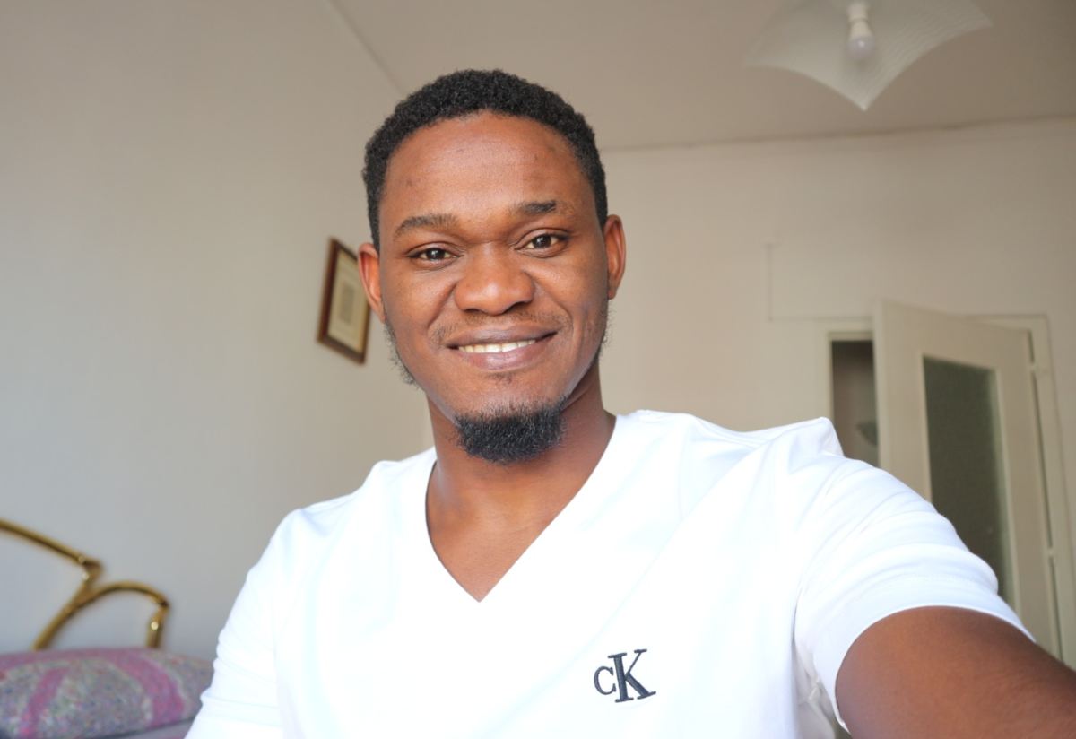 Henry Tbilisi, wearing a white shirt, poses for a selfie in his apartment.