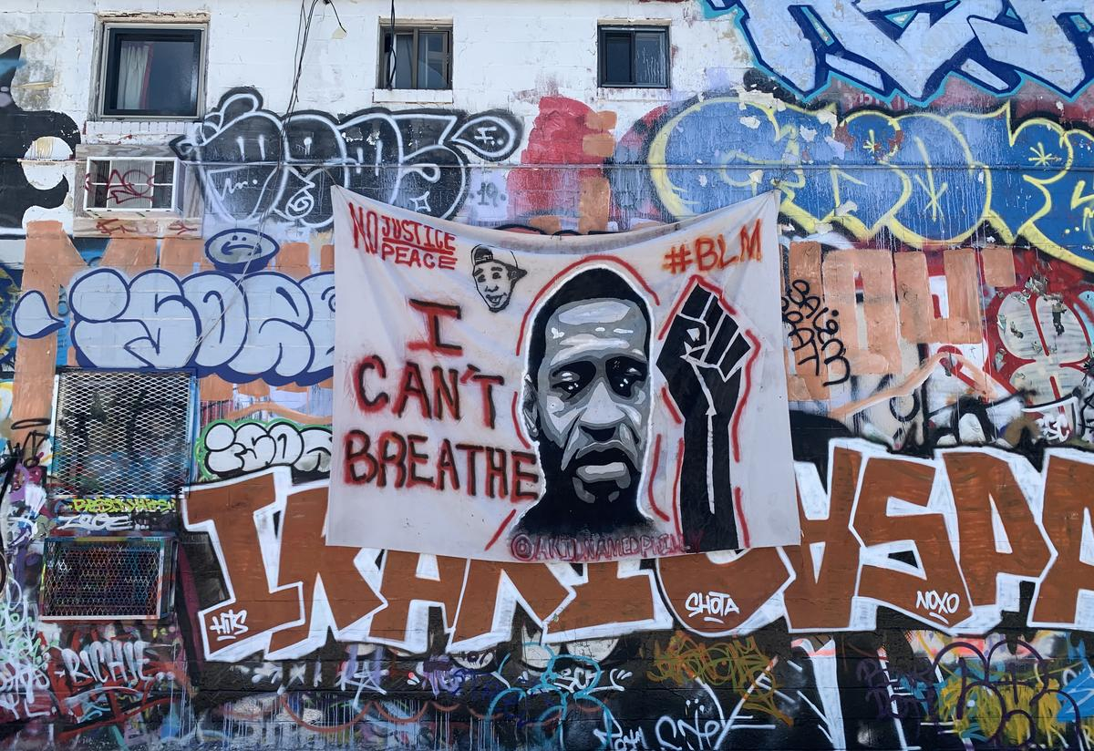 """Banner of George Floyd displayed in """"Graffiti Alley"""" opposite the IRC's Baltimore office."""