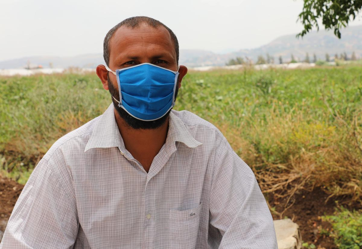 Mohamad sits on the ground and looks at the camera. He has on a white shirt and blue mask.