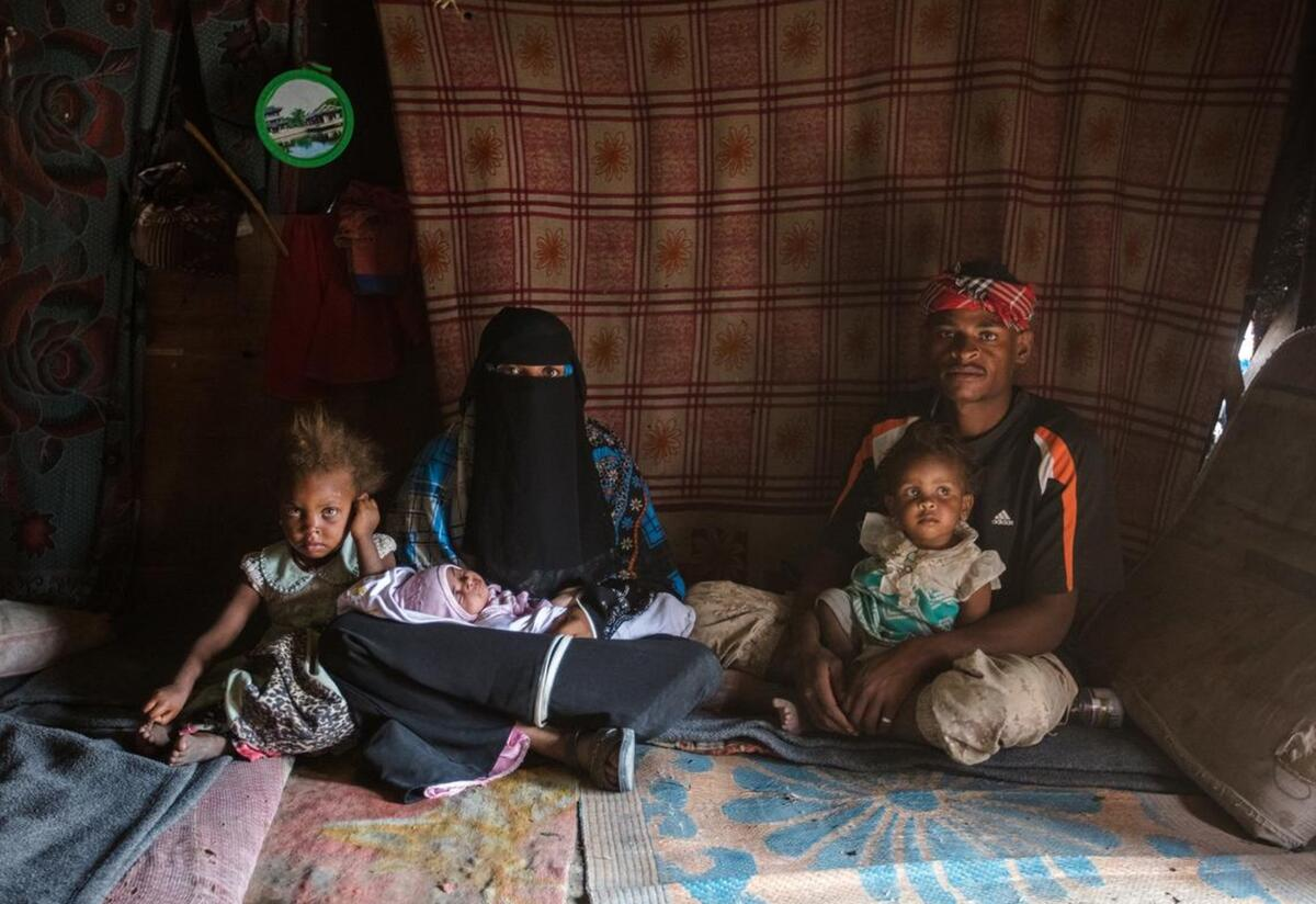 Bodor, 28, holding her baby daughter Enqath, sits with her husband and two children inside their tent. The baby is sitting on Bodor's lap and another child sits on her husband's lap. The whole family is looking at the camera.