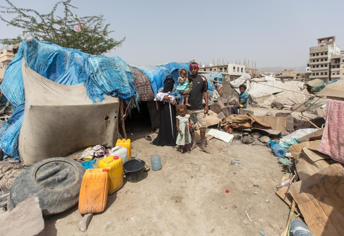 Bodor and her family stand together outside of the displacement camp where they live in the Al Dhale'e region in Yemen. They are standing in front of a makeshift tent.