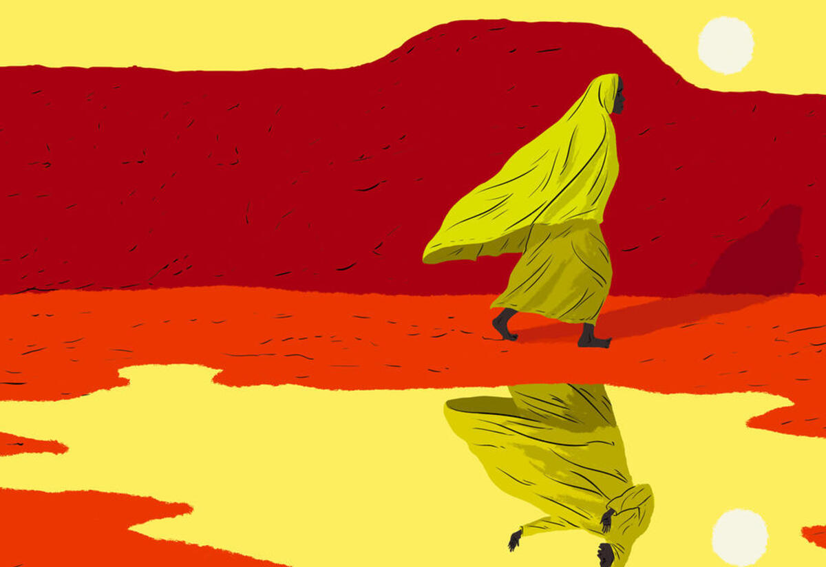 Marie, a woman who journeyed from Cameroon to Niger, walks next to a lake that shows her reflection. She is wearing a yellow head scarf and there is a red mountain behind her.